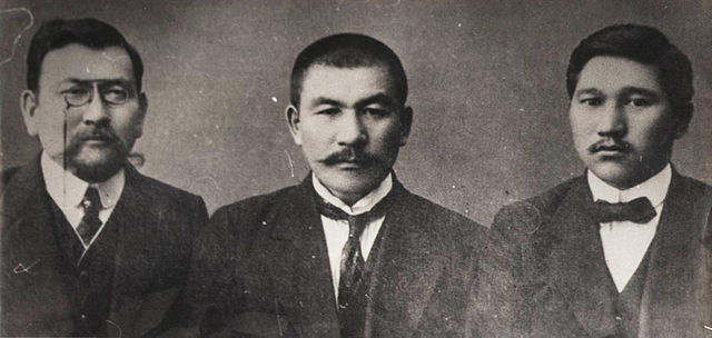 An image of three Asian men sitting together. The man on the left is wearing glasses. They all have mustaches and are wearing suits